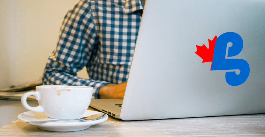 man looking at laptop computer with coffee beside the computer