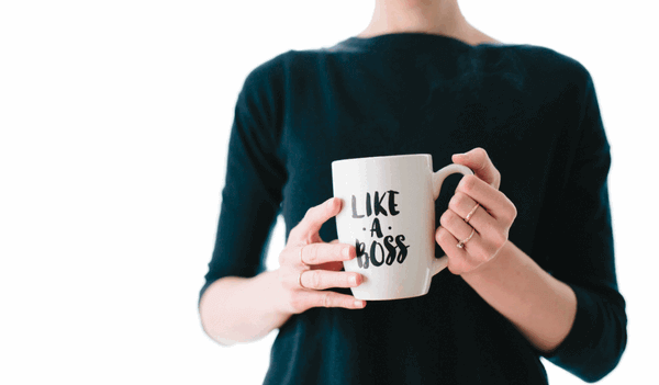 "close up of a female holding a coffee cup that has ""Like A Boss"" on it"